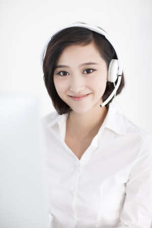 handsfree telephone: Cheerful businesswoman with headset in office