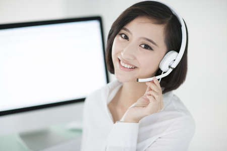 Cheerful businesswoman with headset in office