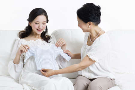Mother and daughter preparing baby clothing LANG_EVOIMAGES