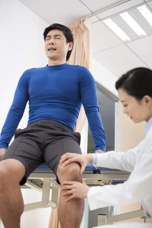 Doctor examining patients leg LANG_EVOIMAGES