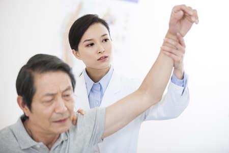 Female doctor examining senior patient