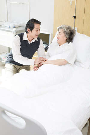 gurney: Senior man taking care of wife in hospital