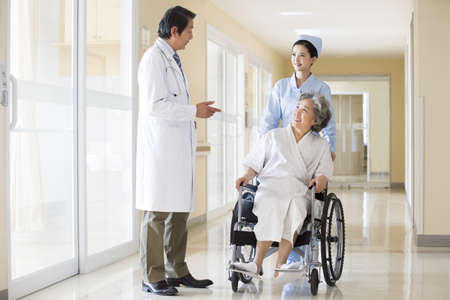 Medical workers taking care of senior woman in wheel chair