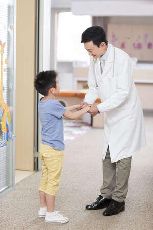 Doctor talking to little boy in hospital LANG_EVOIMAGES