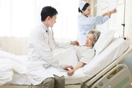 Doctor using stethoscope on patient in hospital