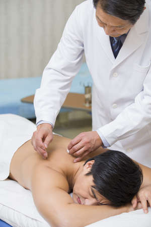Senior doctor giving acupuncture LANG_EVOIMAGES