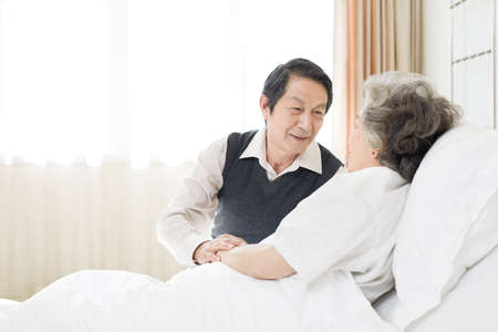 Senior man taking care of wife in hospital