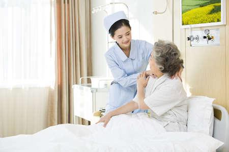 Nurse giving shoulder massage to senior woman in hospital