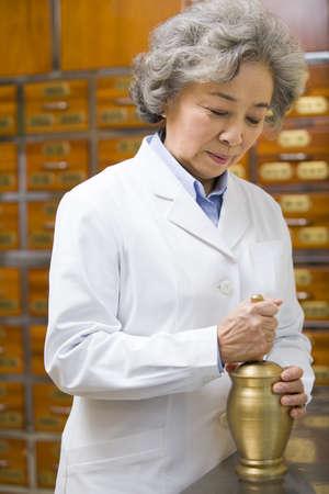 Senior doctor grinding medicinal herbs