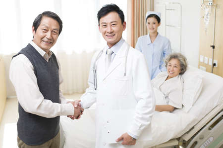 gurney: Senior couple shaking hands with doctor in hospital