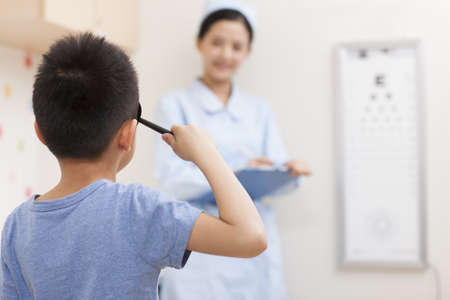 private room: Boy having eye exam LANG_EVOIMAGES