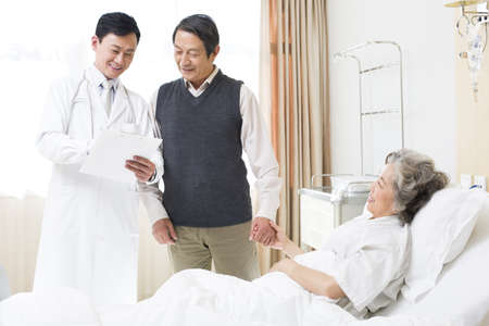 gurney: Doctor with senior couple in hospital LANG_EVOIMAGES