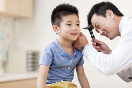 Doctor examining boys ears