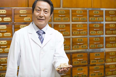 Senior doctor with various medicinal herbs