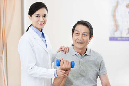 Senior patient exercising with dumbbell under doctors help LANG_EVOIMAGES
