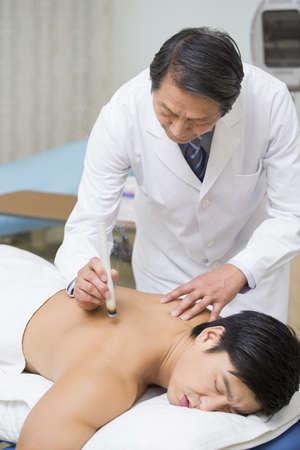 Senior doctor giving moxibustion LANG_EVOIMAGES
