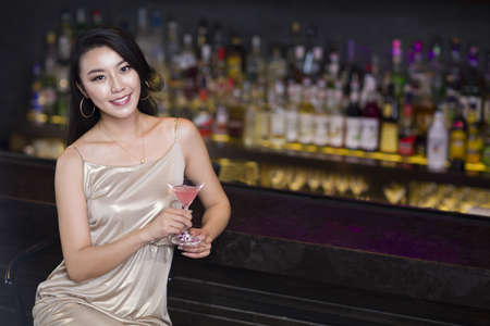 drinks after work: Young woman sitting at bar counter LANG_EVOIMAGES