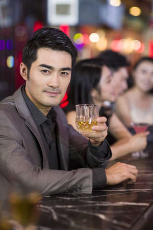 Young man drinking alcohol in bar LANG_EVOIMAGES