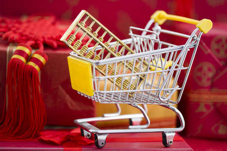 Abacus in shopping cart and many red gift boxes