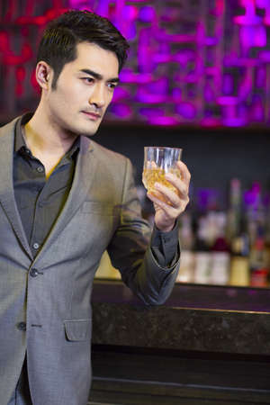 drinks after work: Young man having a drink at bar