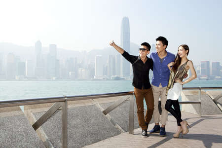Fashionable young friends taking self-portrait pictures with smart phone in Victoria Harbor,Hong Kong