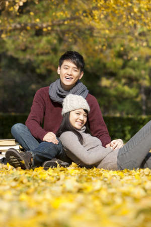 Sweet college couple with books enjoying the nice autumn day on campus