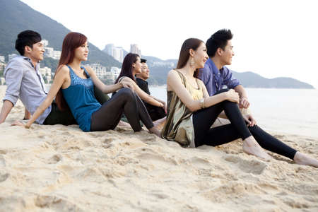 Happy young people sitting on the beach of Repulse Bay,looking at view,Hong Kong