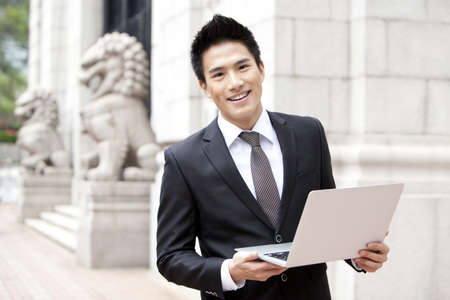 business: Cheerful young businessman with a laptop outside a building,Hong Kong