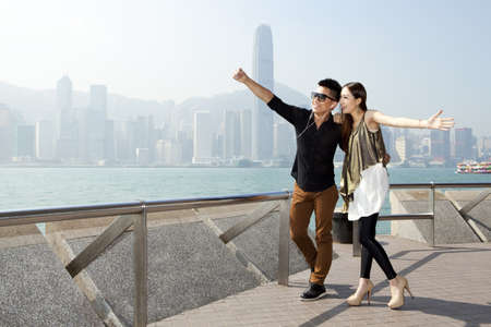Fashionable young couple taking self-portrait pictures with smart phone in Victoria Harbor,Hong Kong