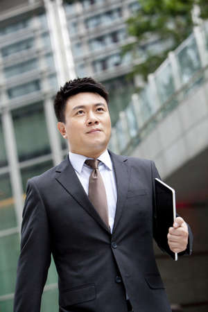 business: Confident mature businessman walking with digital tablet in hand,Hong Kong