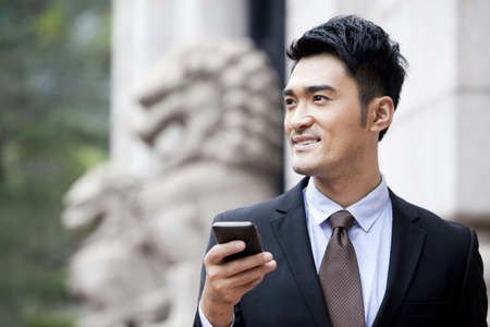 business: Confident businessman with smart phone looking at view,Hong Kong