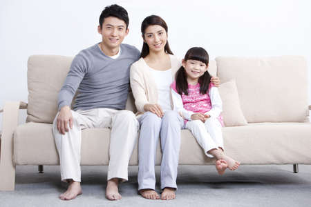 Portrait of happy young family sitting in sofa LANG_EVOIMAGES