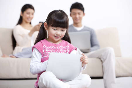 family: Young family using electronic gadgets in living room