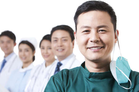 Portrait of happy male surgeon with medical team in background LANG_EVOIMAGES