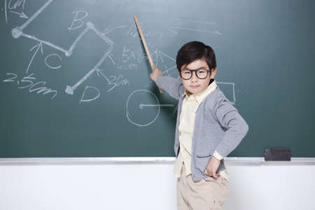 Active little boy playing teacher in classroom LANG_EVOIMAGES