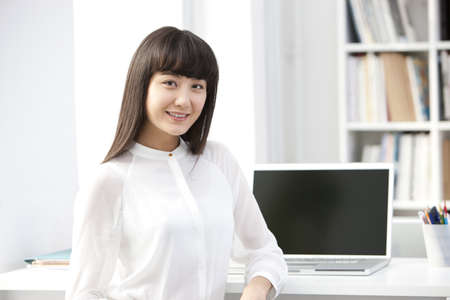Portrait of happy young businesswoman in the office LANG_EVOIMAGES