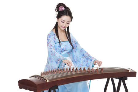 Young woman in Chinese traditional costume plucking Chinese zither