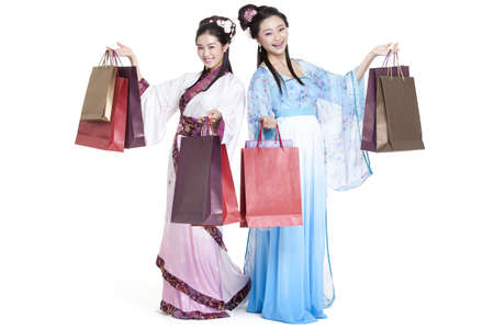 Cheerful young women in traditional Chinese costume with shopping bags