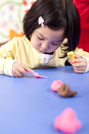 pinching: Kindergarten teachers and children playing with childs play clay