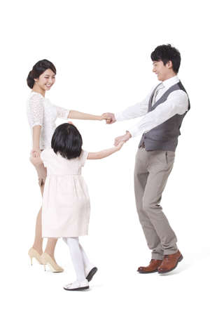 Happy young family spinning in circle,hand in hand
