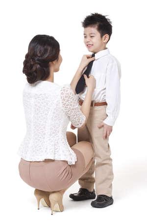 Mother tying necktie for son