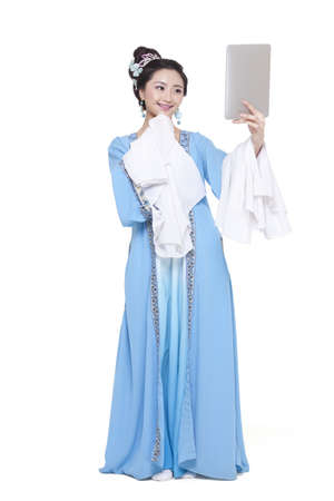 Young woman in traditional Chinese costume holding digital tablet