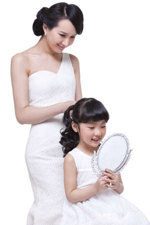 Beautiful mother tying up little daughters hair LANG_EVOIMAGES