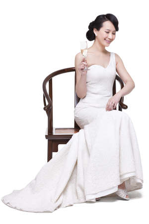 Elegant young woman sitting on Chinese Ming-style wooden armchair with champagne flute
