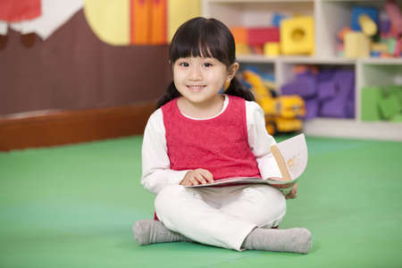 Cute little girl sitting on floor with book in hand