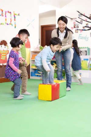 cheer full: Cheerful kindergarten children playing games with teacher LANG_EVOIMAGES
