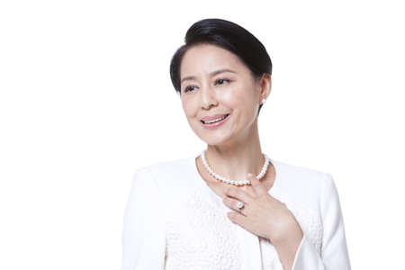 Cheerful mature woman touching her necklace