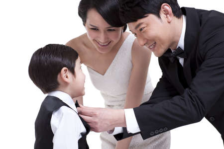 Smiling father adjusting bow tie for little son