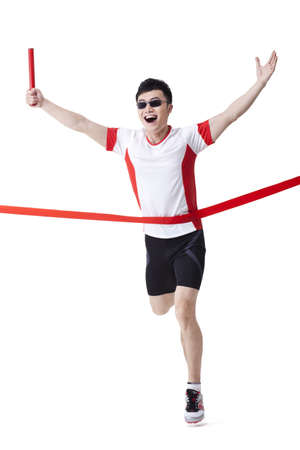 carrera de relevos: Male athlete with relay baton reaching the finish line LANG_EVOIMAGES