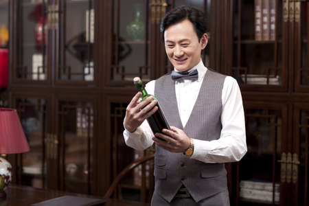 Wealthy businessman with red wine bottle